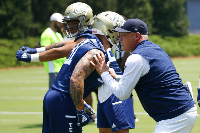 Georgia Tech head coach Geoff Collins works with his players during the team's first preseason NCAA college football practice Wednesday, July 31, 2019, in Atlanta.  (AP Photo/John Bazemore)