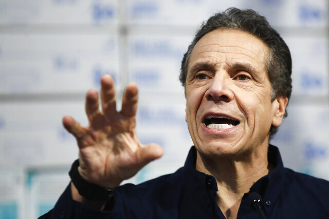 In this March 24, 2020 photo, New York Gov. Andrew Cuomo speaks during a news conference against a backdrop of medical supplies at the Jacob Javits Center that will house a temporary hospital in response to the COVID-19 outbreak in New York. Amid an unprecedented public health crisis, the nation's governors are trying to get what they need from the federal government – and fast. But often that means navigating the disorienting politics of dealing with President Donald Trump. (AP Photo/John Minchillo)