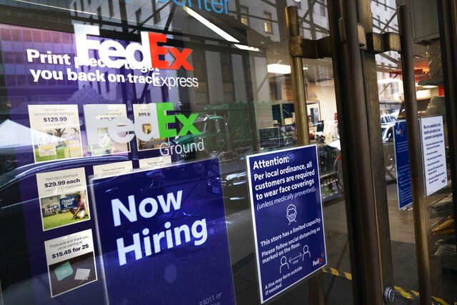 A sign in the window of a FedEx office reads,