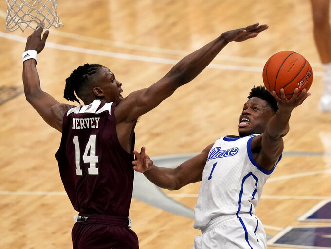Drake's Joseph Yesufu (1) shoots as Missouri State's Keaton Hervey (14) defends during the first half of an NCAA college basketball game in the semifinal round of the Missouri Valley Conference men's tournament Saturday, March 6, 2021, in St. Louis. (AP Photo/Jeff Roberson)
