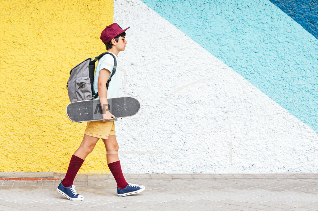 Boy with backpack and skateboard walking by multi colored wall