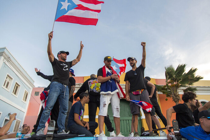 Singer Ricky Martin, left, waves the Puerto Rican flag during march against governor Ricardo Rosello, in San Juan, Puerto Rico, Wednesday, July 17, 2019. Protesters are demanding Rossello step down for his involvement in a private chat in which he used profanities to describe an ex-New York City councilwoman and a federal control board overseeing the island's finance. (AP Photo/Dennis M. Rivera Pichardo)