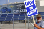 FILE - In this Sept. 16, 2019, file photo a picketer carries sign at one of the gates outside the closed General Motors automobile assembly plant in Lordstown, Ohio. A tentative four year contract with striking General Motors gives workers a mix of pay raises, lump sum payments and an $11,000 signing bonus. In return, the contract allows GM to proceed with factory closures in Lordstown, Ohio, Warren, Mich., and near Baltimore. (AP Photo/Keith Srakocic, File)