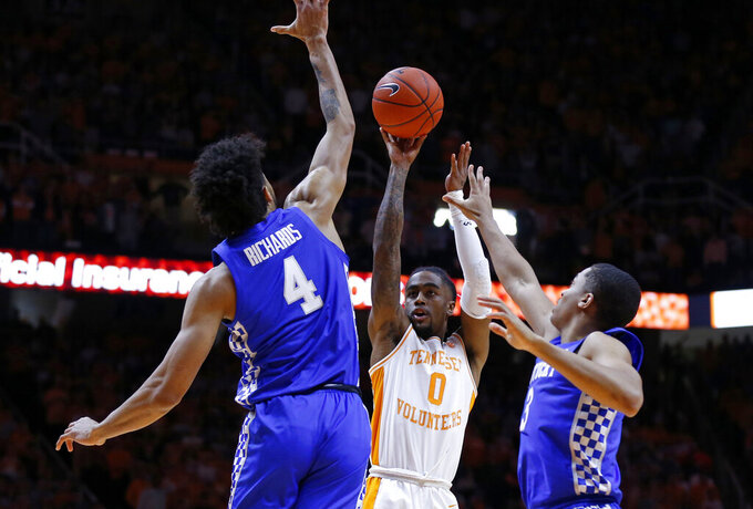 Tennessee guard Jordan Bone (0) shoots over Kentucky forward Nick Richards (4) and guard Keldon Johnson (3) during the first half of an NCAA college basketball game Saturday, March 2, 2019, in Knoxville, Tenn. (AP Photo/Wade Payne)