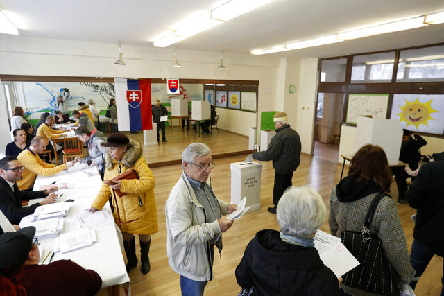 People vote at a polling station during general elections in Trnava, Slovakia, Saturday, Feb. 29, 2020. Slovaks vote Saturday in parliamentary elections widely expected to unseat the country's long-dominant but scandal-tainted center-left party that governed on an anti-immigration platform, in favor of a coalition headed by center-right populists. (AP Photo/Petr David Josek)