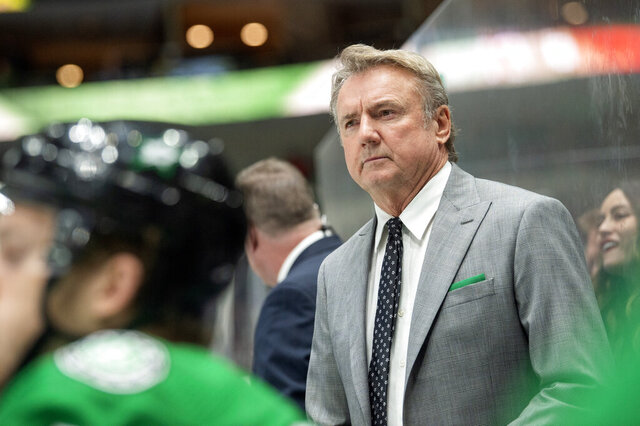 FILE - In this Tuesday, Dec. 10, 2019 file photo, Dallas Stars interim head coach Rick Bowness watches play from behind the bench during the third period of an NHL hockey game against the New Jersey Devils, Tuesday, Dec. 10, 2019, in Dallas. The Dallas Stars were in a miserable stretch when the NHL season came to a sudden and unexpected stop 4 1/2 months ago. Vegas was playing some of its best hockey after a coaching change. Both now have the same chance of being the No. 1 seed in the Western Conference playoffs, and a better chance to re-acclimate to playing again than having to jump right into a playoff series for the resumption of this unprecedented season because of the coronavirus (AP Photo/Jeffrey McWhorter, File)