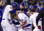 Los Angeles Dodgers' Joc Pederson, below, celebrates with teammates as he scores after hitting a walk-off, two-run home run during the ninth inning of a baseball game against the Cincinnati Reds, Monday, April 15, 2019, in Los Angeles. (AP Photo/Mark J. Terrill)