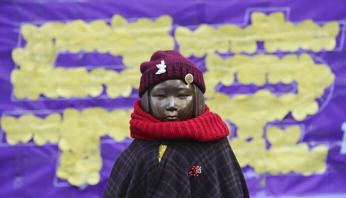 """FILE - In this Dec. 28, 2017, file photo, a statue representing sex slaves is seen near the Japanese Embassy in Seoul, South Korea. Japan's army during World War II asked the government to provide one sex slave for every 70 soldiers, according to historical documents reviewed by Kyodo News service that highlight the state role in the so-called """"comfort women"""" system. The letters read"""