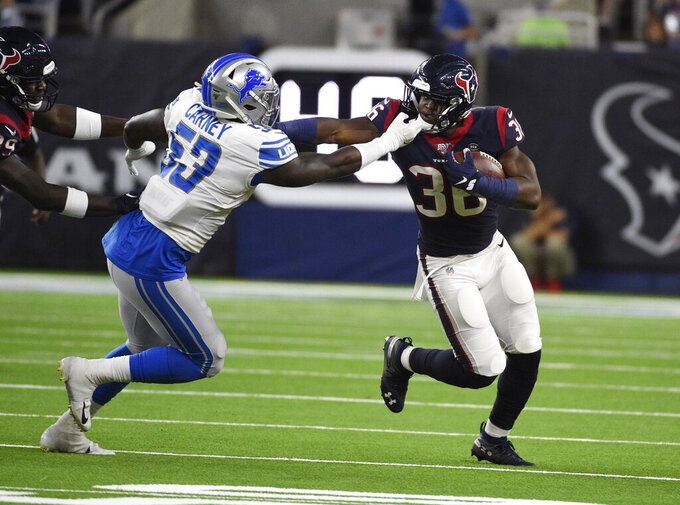 Detroit Lions linebacker Malik Carney (53) grabs the facemask of Houston Texans running back Damarea Crockett (36) during the second half of an NFL preseason football game Saturday, Aug. 17, 2019, in Houston. (AP Photo/Eric Christian Smith)