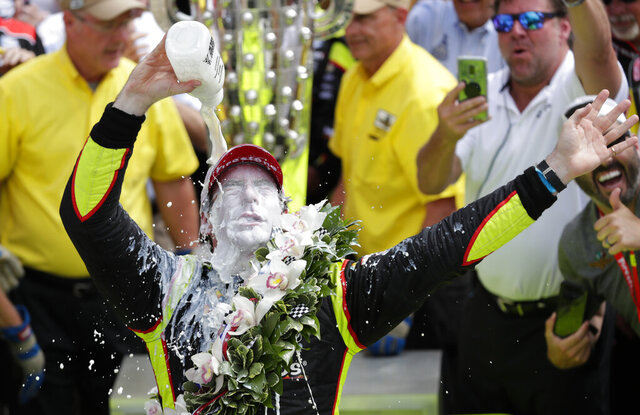 FILE - This May 26, 2019, file photo shows Simon Pagenaud, of France, celebrating after winning the Indianapolis 500 IndyCar auto race at Indianapolis Motor Speedway, in Indianapolis.  The Indy 500 has been rescheduled for Aug. 23, 2020, and won't be run on Memorial Day weekend as scheduled for the first time since its return in 1946. Pagenaud passed Alexander Rossi on the penultimate lap to win last May. That gave Roger Penske his 18th win at Indy on the 50th anniversary of his arrival at the Brickyard and before he became the series and track owner. (AP Photo/Michael Conroy, File)
