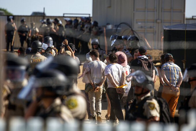 Activists are escorted out of an Enbridge Line 3 pump station after being arrested near Park Rapids, Minn., on Monday, June 7, 2021. (Evan Frost/Minnesota Public Radio via AP)