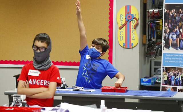 FILE - In this July 14, 2020, file photo, amid concerns of the spread of COVID-19, Aiden Trabucco, right, wears a mask as he raises his hand to answer a question behind Anthony Gonzales during a summer STEM camp at Wylie High School in Wylie, Texas. School districts that plan to reopen classrooms in the fall are wrestling with whether to require teachers and students to wear face masks — an issue that has divided urban and rural schools and yielded widely varying guidance. (AP Photo/LM Otero, File)