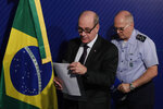 Brazil's Defense Minister Fernando Azevedo e Silva, left, and the Commander of the Brazilian Air Force Antonio Carlos Moretti Bermudez walk off the stage after a press conference regarding an Air Force sergeant accused of trying to smuggle cocaine into Spain, at the headquarters of the Ministry of Defense in Brasilia, Brazil, Thursday, June 27, 2019. Brazilian officials are confirming the sergeant was working on a support mission for President Jair Bolsonaro's trip to the G-20 summit in Japan. (AP Photo/Eraldo Peres)