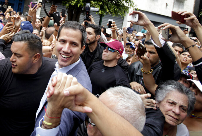 Venezuela's self-proclaimed interim president Juan Guaido greets supporters at a rally in Los Teques, Miranda State, Venezuela, Saturday, March 30, 2019. Guaido took his campaign for change to one of the country's most populous states on Saturday, while supporters of the man he is trying to oust, President Nicolas Maduro, held a rival demonstration in the capital after another nationwide blackout. (AP Photo/Boris Vergara)