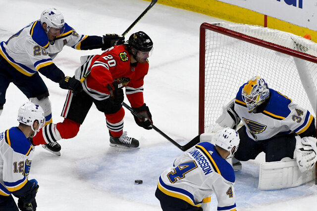 St. Louis Blues goaltender Jake Allen (34), defenseman Carl Gunnarsson (4) and left wing Alexander Steen (20) defend against Chicago Blackhawks left wing Brandon Saad (20) during the second period of an NHL hockey game between the Chicago Blackhawks and the St. Louis Blues on Sunday March 8, 2020, in Chicago. (AP Photo/Matt Marton)