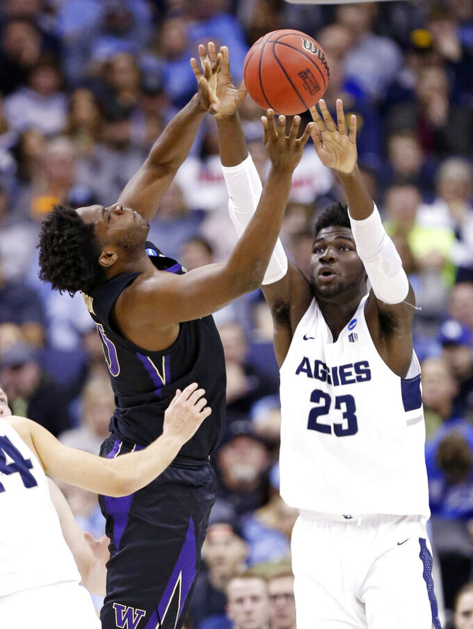 Utah State's Neemias Queta (23) passes over Washington's Noah Dickerson (15) in the first half during a first round men's college basketball game in the NCAA Tournament in Columbus, Ohio, Friday, March 22, 2019. (AP Photo/Paul Vernon)