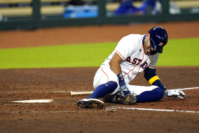 Houston Astros' Carlos Correa reacts after fouling a pitch off his leg during the sixth inning of a baseball game against the Texas Rangers Tuesday, Sept. 15, 2020, in Houston. Correa left the game after the injury. (AP Photo/David J. Phillip)