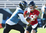 Jacksonville Jaguars quarterback Trevor Lawrence, right, hands off to running back Carlos Hyde during NFL football training camp, Wednesday, July 28, 2021, at the team's practice fields outside TIAA Bank Field in Jacksonville, Fla. (Bob Self/The Florida Times-Union via AP)
