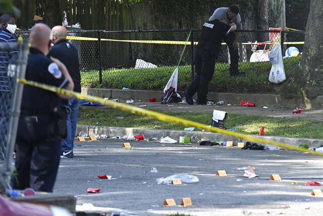 Authorities investigate the scene in the Greenway neighborhood in Southeast Washington after an early-morning shooting left at least 21 wounded as hundreds attended the neighborhood's block party in Washington, DC on Sunday, August 9, 2020. (Marvin Joseph/The Washington Post via AP)