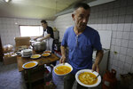 In this photo taken on Sunday, June 10, 2018, Bosnian people prepare lunch for migrants in Velika Kladusa, 400 kms north west of Bosnian capital of Sarajevo. The restaurant owner Asim Latic from northwestern Bosnia in February closed down his pizzeria for regular guests and is now serving only meals for migrants passing through the Balkan nation while trying to reach Western Europe. (AP Photo/Amel Emric)