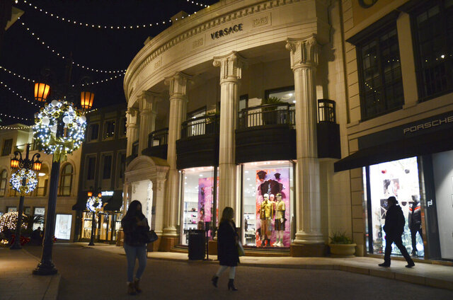 People walk near the Versace boutique on Rodeo Drive, decorated for the holidays amid the coronavirus pandemic, Monday, Nov. 30, 2020, in Beverly Hills, Calif. The three-week