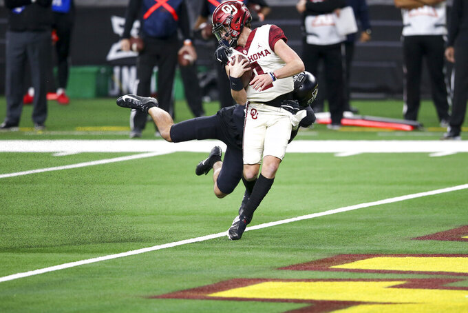 Oklahoma quarterback Chandler Morris (4) runs in for a touchdown in front of Iowa State defensive back Greg Eisworth II during the first half of the the Big 12 Conference championship NCAA college football game, Saturday, Dec. 19, 2020, in Arlington, Texas.(Ian Maule/Tulsa World via AP)