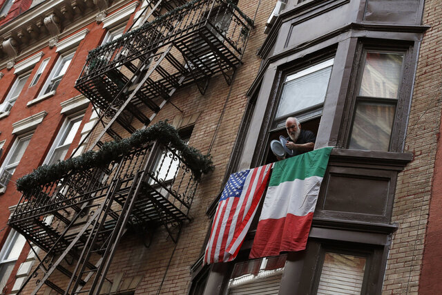 A man leans out the window on Mulberry Street in New York's Little Italy and bangs together pot lids to show his support for those in the front lines fighting against the coronavirus pandemic, Monday, April 13, 2020. Citywide people open their windows each evening at 7 p.m. to make noise to support the doctors, nurses, hospital staff, EMT's and front-line workers who are risking their lives every day. (AP Photo/Mark Lennihan)