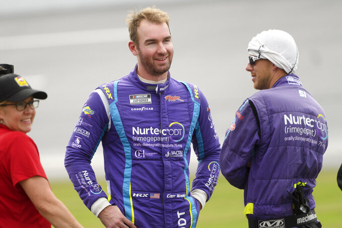 Cody Ware talks with team members while waiting to restart a NASCAR Cup series auto race during a rain delay Monday, Oct. 4, 2021, in Talladega, Ala. (AP Photo/John Amis)
