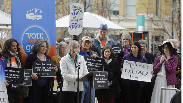 People gather outside the office of Senator Mitt Romney to call on him to push for a full and fair impeachment trial in the Senate with pertinent testimony and evidence during a rally Thursday, Jan. 16, 2020, in Salt Lake City. (AP Photo/Rick Bowmer)