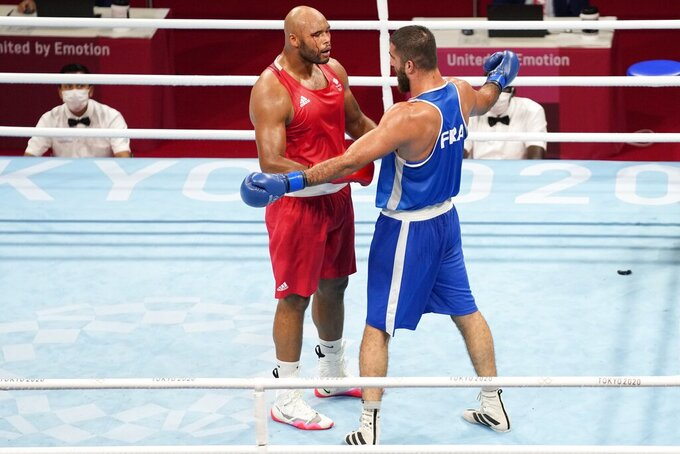 Eliad Mourad, of France talks to Britain's Frazer Clarke after being disqualified during a men's super heavyweight over 91-kg boxing match at the 2020 Summer Olympics, Sunday, Aug. 1, 2021, in Tokyo, Japan. (AP Photo/Frank Franklin II)