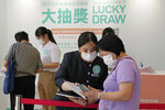 In this Tuesday, June 15, 2021, photo, people wearing face masks to help prevent the spread of the coronavirus, register for a lottery in a Grand Central residential building complex in Hong Kong. Coronavirus vaccine incentives offered by Hong Kong companies, including a lucky draw for an apartment, a Tesla car and even gold bars, are helping boost the city's sluggish inoculation rate. (AP Photo/Kin Cheung)