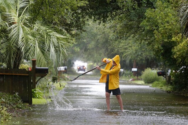FILE - In this Thursday, Sept. 5, 2019, file photo, an Isle of Palms resident clears the drain on Hartnett Blvd. during Hurricane Dorian at the Isle of Palms, S.C., in Charleston, S.C. (AP Photo/Mic Smith, File)