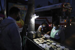 """Gertrudis Hernandez sells """"pupusas"""" at a bus stop in San Salvador, El Salvador, before sunrise Tuesday, Sept. 7, 2021, on the day all businesses have to accept payments in Bitcoin, except those lacking the technology to do so. Hernandez said she'll learn how to use Bitcoin when needed, just like the dollar. (AP Photo/Salvador Melendez)"""