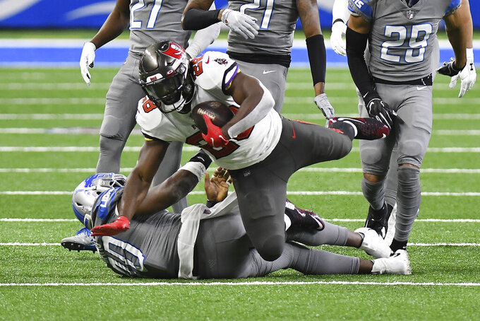 Tampa Bay Buccaneers running back Leonard Fournette (28) trips over Detroit Lions middle linebacker Jarrad Davis (40) during the first half of an NFL football game, Saturday, Dec. 26, 2020, in Detroit. (AP Photo/Lon Horwedel)