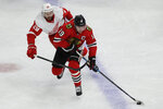 Chicago Blackhawks center Jonathan Toews, right, looks to pass against Detroit Red Wings left wing Brendan Perlini during the first period of an NHL hockey game in Chicago, Sunday, Jan. 5, 2020. (AP Photo/Nam Y. Huh)