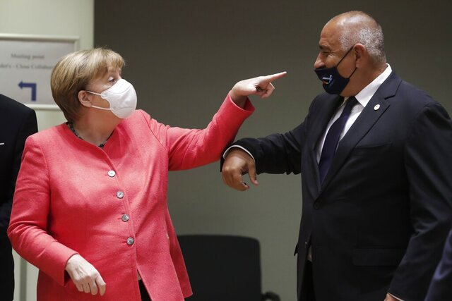 German Chancellor Angela Merkel, left, speaks with Bulgaria's Prime Minister Boyko Borissov during a round table meeting at an EU summit in Brussels, Friday, July 17, 2020. Leaders from 27 European Union nations meet face-to-face on Friday for the first time since February, despite the dangers of the coronavirus pandemic, to assess an overall budget and recovery package spread over seven years estimated at some 1.75 trillion to 1.85 trillion euros. (Stephanie Lecocq, Pool Photo via AP)