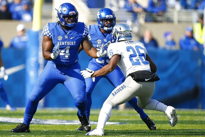 In this Nov. 17, 2018, photo, Kentucky NCAA college football defensive end Joshua Paschal (4) blocks against Middle Tennessee linebacker Wayne Parks (26) during a game at Kroger Field in Lexington, Ky. Paschal is a cancer survivor, having completed treatment in August, 2019, about a year after what he thought was a blister on the bottom of his foot turned out to be a malignant melanoma. Paschal is one of 30 nominees for the Mayo Clinic Comeback Player of the Year Award. (Alex Slitz/Lexington Herald-Leader via AP)
