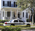 An Osceola County Sheriff's Office patrol car is posted outside a home in Celebration, an affluent community, Wednesday, Jan. 15, 2020, in Kissimmee, Fla. Authorities in Florida have charged a physical therapist with killing his wife, their three young children and a dog in the affluent suburb near Walt Disney World. The bodies were discovered Monday in the rental home that sold last April. (Joe Burbank/Orlando Sentinel via AP)