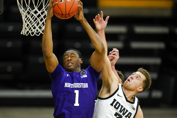 Northwestern guard Chase Audige (1) fights for a rebound with Iowa guard Jordan Bohannon, right, during the first half of an NCAA college basketball game, Tuesday, Dec. 29, 2020, in Iowa City, Iowa. (AP Photo/Charlie Neibergall)