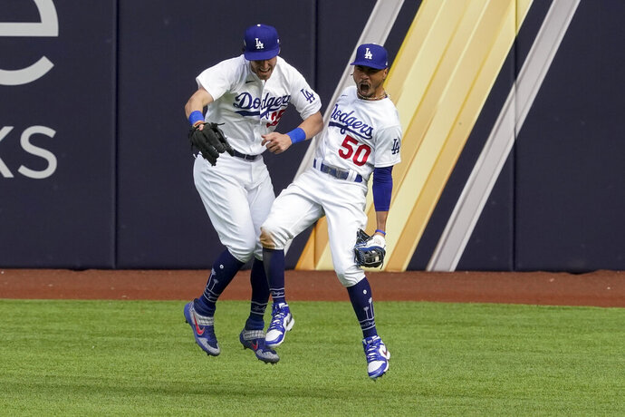 Los Angeles Dodgers right fielder Mookie Betts celebrates with center fielder Cody Bellinger after robbing Atlanta Braves' Marcell Ozuna of a home during the fifth inning in Game 6 of a baseball National League Championship Series Saturday, Oct. 17, 2020, in Arlington, Texas. (AP Photo/Tony Gutierrez)