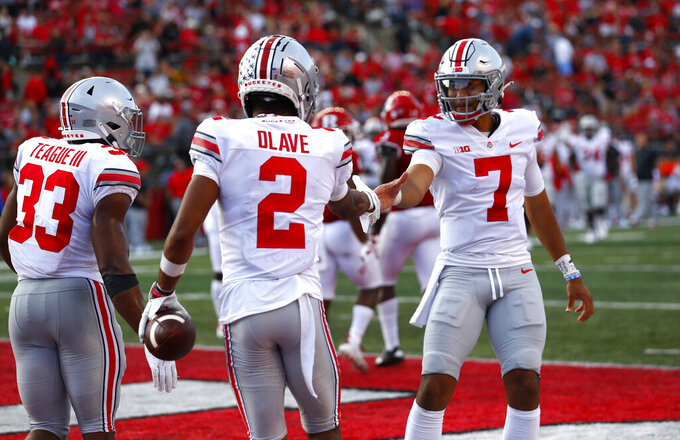 Ohio State quarterback C.J. Stroud (7) shakes hands with wide receiver Chris Olave (2) after Olave's touchdown reception against Rutgers during an NCAA college football game, Saturday, Oct. 2, 2021, in Piscataway, N.J. Ohio State won 52-13. (AP Photo/Noah K. Murray)