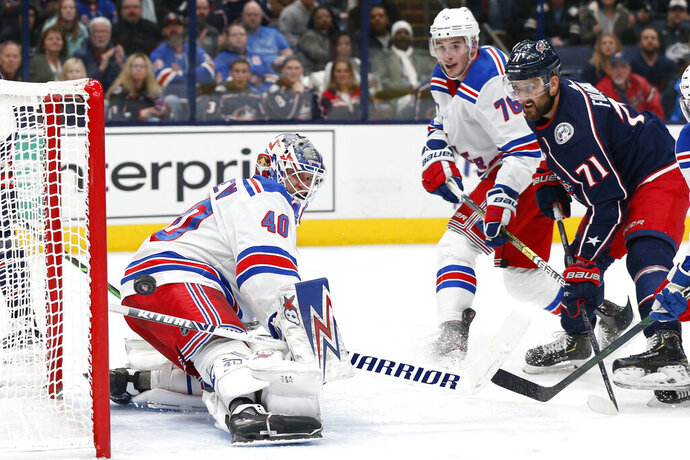 New York Rangers' Alexandar Georgiev, left, makes a save as Brady Skjei, center, and Columbus Blue Jackets' Nick Foligno watch the puck during the second period of an NHL hockey game Friday, Feb. 14, 2020, in Columbus, Ohio. (AP Photo/Jay LaPrete)