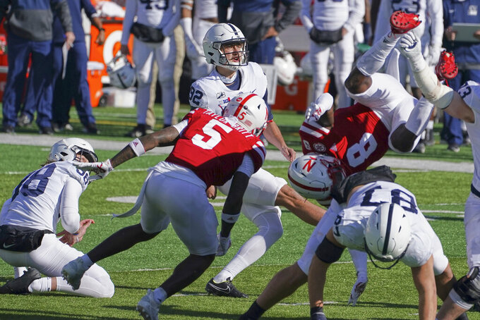 Penn State kicker Jake Pinegar (92) kicks a field goal with Penn State's Jordan Stout (98) holding, as Nebraska's Deontai Williams (8) and Cam Taylor-Britt (5) defend during the first half of an NCAA college football game in Lincoln, Neb., Saturday, Nov. 14, 2020. (AP Photo/Nati Harnik)