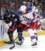 Columbus Blue Jackets' Boone Jenner, left, and New York Rangers' Jacob Trouba fight for the puck during the second period of an NHL hockey game Thursday, Dec. 5, 2019, in Columbus, Ohio. (AP Photo/Jay LaPrete)