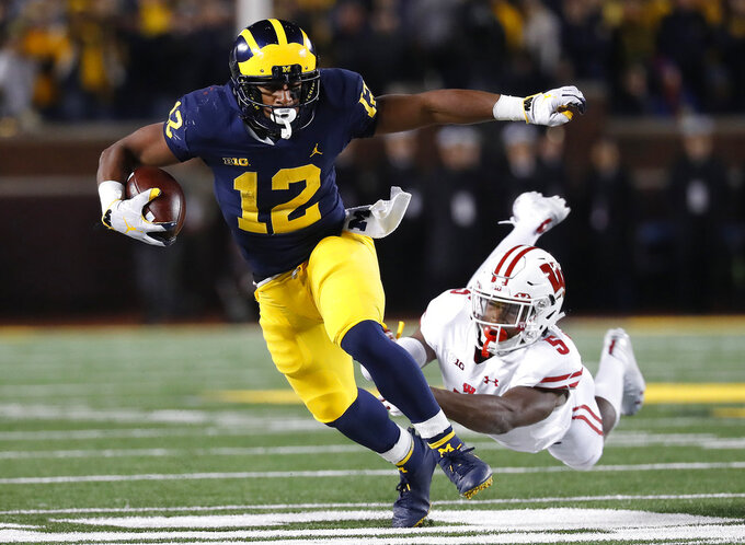 File-This Oct. 13, 2018, shows Michigan running back Chris Evans (12) shaking the tackle of Wisconsin cornerback Rachad Wildgoose (5) during the second half of an NCAA college football game in Ann Arbor, Mich. Evans, a junior, may lead Michigan's running back committee in the Peach Bowl, that also is expected to include Tru Wilson and Christian Turner.  (AP Photo/Paul Sancya, File)