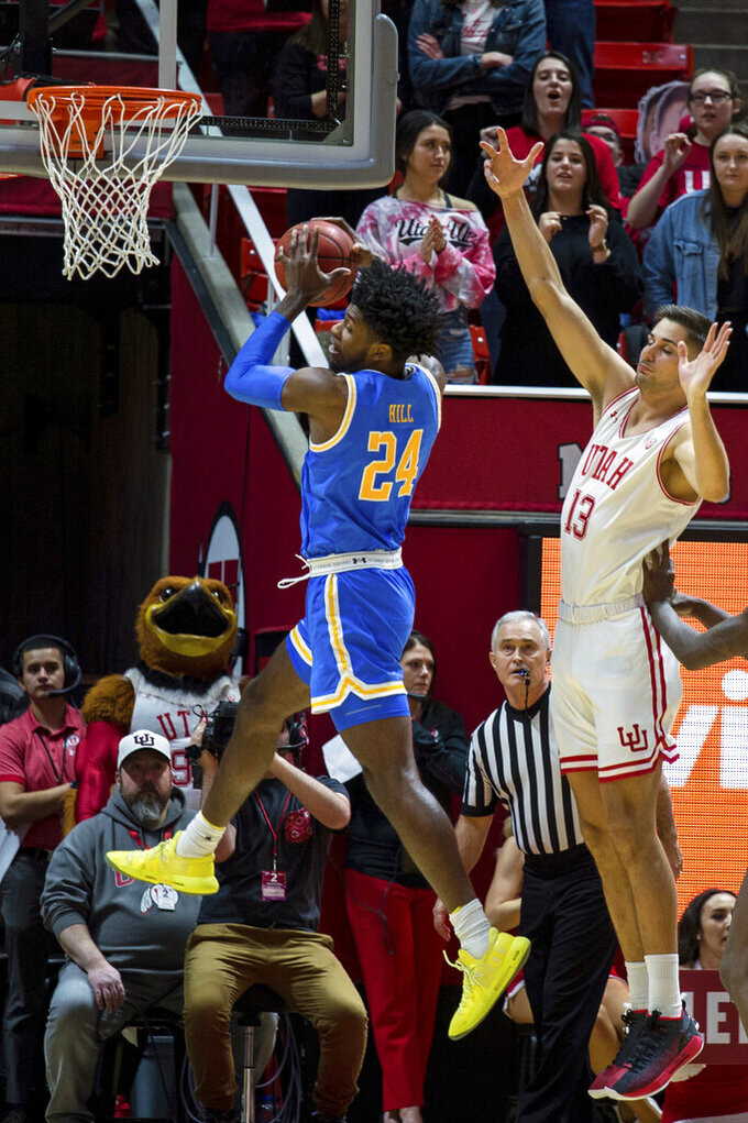 UCLA guard Jalen Hill (24) grabs a rebound against Utah forward Novak Topalovic (13) in the first half of an NCAA college basketball game Saturday, March 9, 2019, in Salt Lake City. (AP Photo/Tyler Tate)