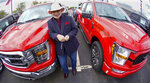 In this photo made on Thursday, May 6, 2021, Shults Ford dealership owner Richard Bazzy stands between two of the remaining Ford F150 pickups on the front line on their dealership lot in Wexford, Pa. Ford is warning that it expects to make only half the normal number of vehicles from now through June. Bazzy normally stocks 400-500 pickup trucks at his three Ford dealers, but is down around 100. He's confident that he can keep customers happy if they can order a truck and get it in four weeks, but he fears losing business to competing brands with a huge stock. (AP Photo/Keith Srakocic)