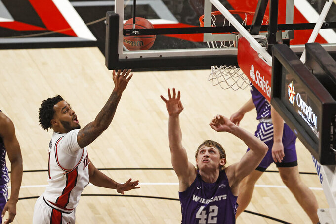 Texas Tech's Kyler Edwards (11) lays up the ball next to Abilene Christian's Clay Gayman (42) during the first half of an NCAA college basketball game Wednesday, Dec. 9, 2020, in Lubbock, Texas. (AP Photo/Brad Tollefson)