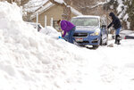 Jennifer Stewart, left, and Amy Holland dig their snow out of a snow bank after swerving to avoid a four-wheeler plowing snow on Wednesday, Feb. 27, 2019, in an alley in Moscow, Idaho. The car was pulled out of the snow bank by a truck that plowing a nearby parking lot. (Geoff Crimmins/Moscow-Pullman Daily News via AP)