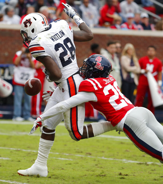 Auburn running back JaTarvious Whitlow (28) is hit from behind by Mississippi defensive back Jalen Julius (26) and fumbles the ball after a 54-yard run,in the second half of an NCAA college football game on Saturday, Oct. 20, 2018, in Oxford, Miss. Whitlow's fumble was recovered in the end zone for a touchdown by Auburn wide receiver Anthony Schwartz (5). Auburn won 31-16. (AP Photo/Rogelio V. Solis)
